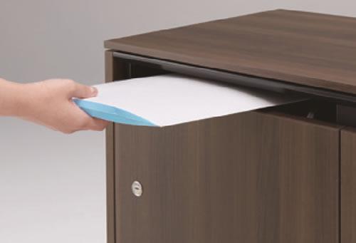 ヨコ型の書類投函口と、その奥に用意された平置きの受け部。書類が曲がらずストックできるので、薄い用紙から分厚い封書やファイル類まで、きれいに保管が可能です。スリットに手を掛ける構造にすることで、錠前部分は鍵穴だけのデザインにこだわった作りにすることも出来ました。